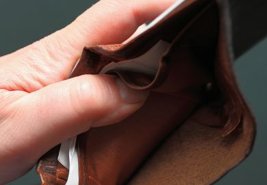 Hand holding battered leather wallet