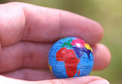 Hand holding globe showing Africa