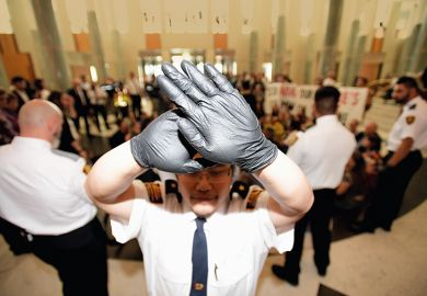 Security guard holds up hands