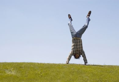 Student handstand on grass