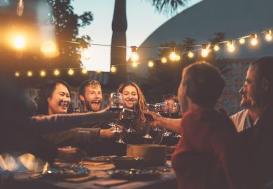 Happy people dining and drinking red wine at barbecue dinner party