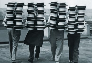 Four people carrying piles of hats
