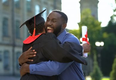 A cheerful father and graduating son hugging