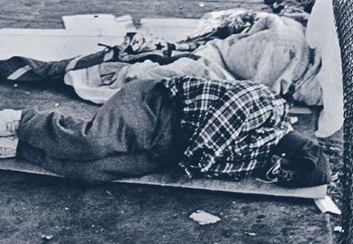 Homeless person asleep on street pavement