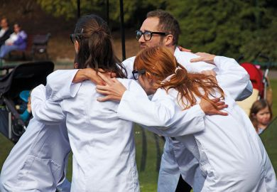 people wearing lab coats huddling together