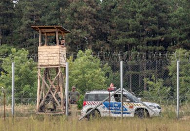 September 10, 2016: Hungarian policemen watching the Serbia Hungarian border fence