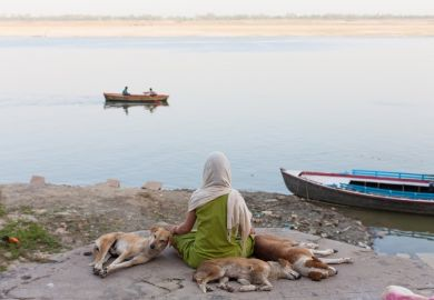 Scarfed young indian woman meditating on the border of the Ganges