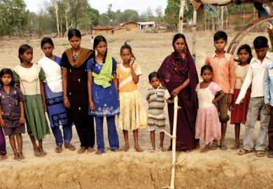 Indian women and children standing beside well