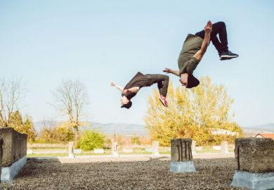 Two people perform backflips illustrating flipped classroom model
