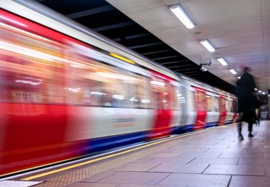 A London Underground train speeds through a station. Lack of commute is a factor in academics reporting satisfaction with homeworking.