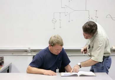 Mature student being shown text by teacher