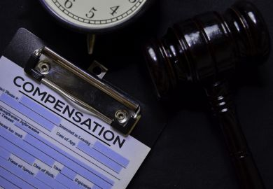 Paperwork for a compensation claim sits on a desk with a gavel