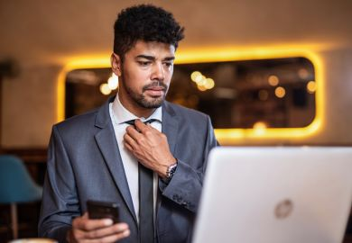 A candidate adjusts his tie before a job interview. Online interviews add an extra layer of difficulty to an already stressful situation.