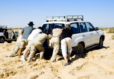 People pushing car stuck in sand