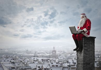 Santa sitting on a chimney with a laptop