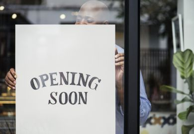 "Man putting ""store opening"" sign in shop window"