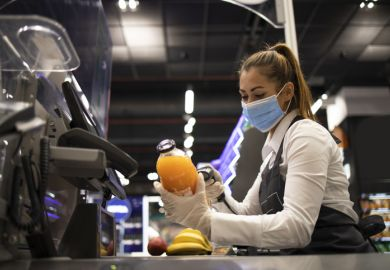 A checkout worker wearing a mask