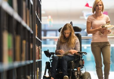 Woman in wheelchair in library