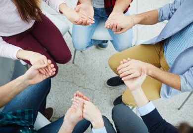 People holding hands, sitting in a circle