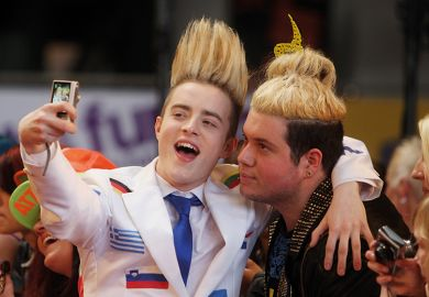 Jedward taking a selfie with a fan illustrating the academic star system