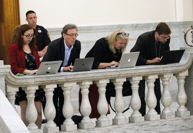 people work on laptops on balcony