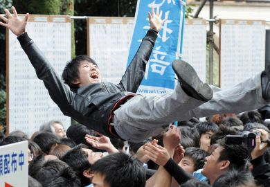 Laughing student being thrown in air by friends