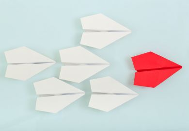 Red paper plane leading white paper planes