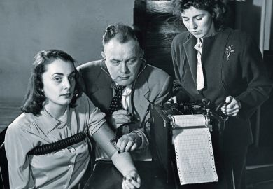 Two researchers conducting a lie detector test on a young woman