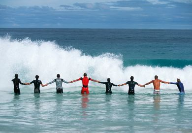 A line of people holding hands facing a wave