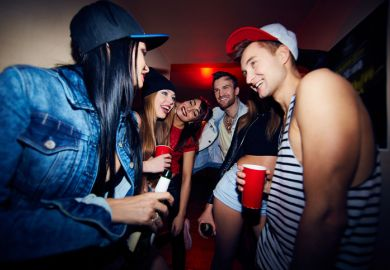 Low angle group of young stylish people standing in dark hall of nightclub together, talking, laughing and drinking beer as they wait to be admitted