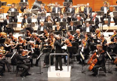 Male conductor conducting orchestral concert