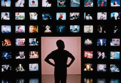 Male silhouette facing wall of television screens
