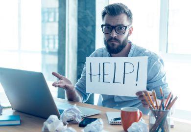 Man at desk holding 'Help' sign