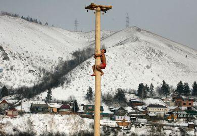 Man climbing wooden column, Krasnoyarsk, Siberia