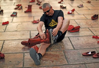 Man compares shoes, La Constitucion Square, Malaga, Spain