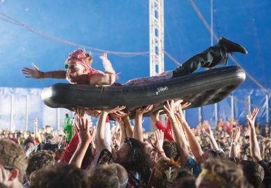 Man crowd surfing on inflatable bed, Bestival 2015, Isle of Wight