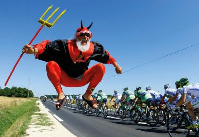 Man dressed as devil jumping beside Tour de France cycling race