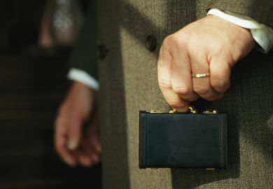 Man holding tiny briefcase between finger and thumb