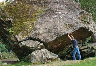 Man holding up rock
