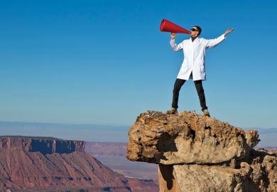 Man in lab coat shouting from rock with megaphone