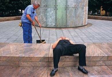 Man lays down while another works behind