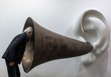 Man looking in to ear horn sculpture