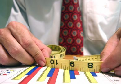 Man measuring bar graphs with tape measure