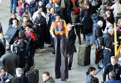 Man on stilts walking through crowd