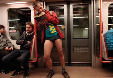 Man reading book on subway train, No Pants Subway Ride, Prague, 2015