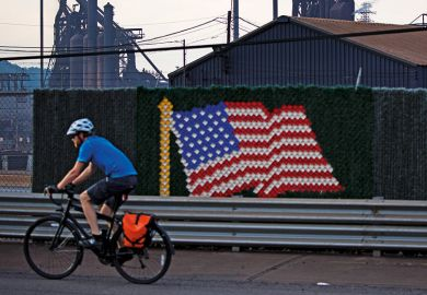 Man riding bicycle past United States of America flag