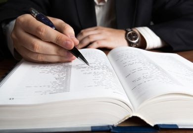 Man scanning dictionary page with pen