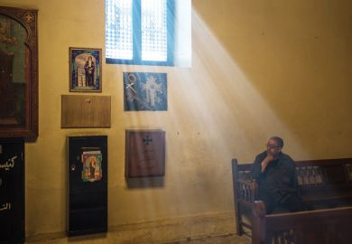 Man sitting in sunlight lit church