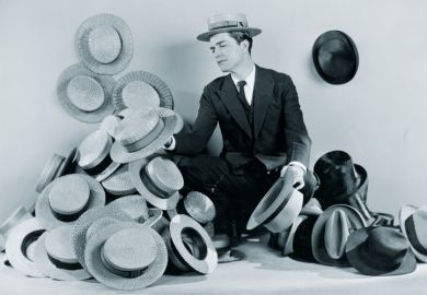 Man sitting on floor surrounded by boater hats