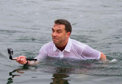 Man standing in water taking selfie photograph
